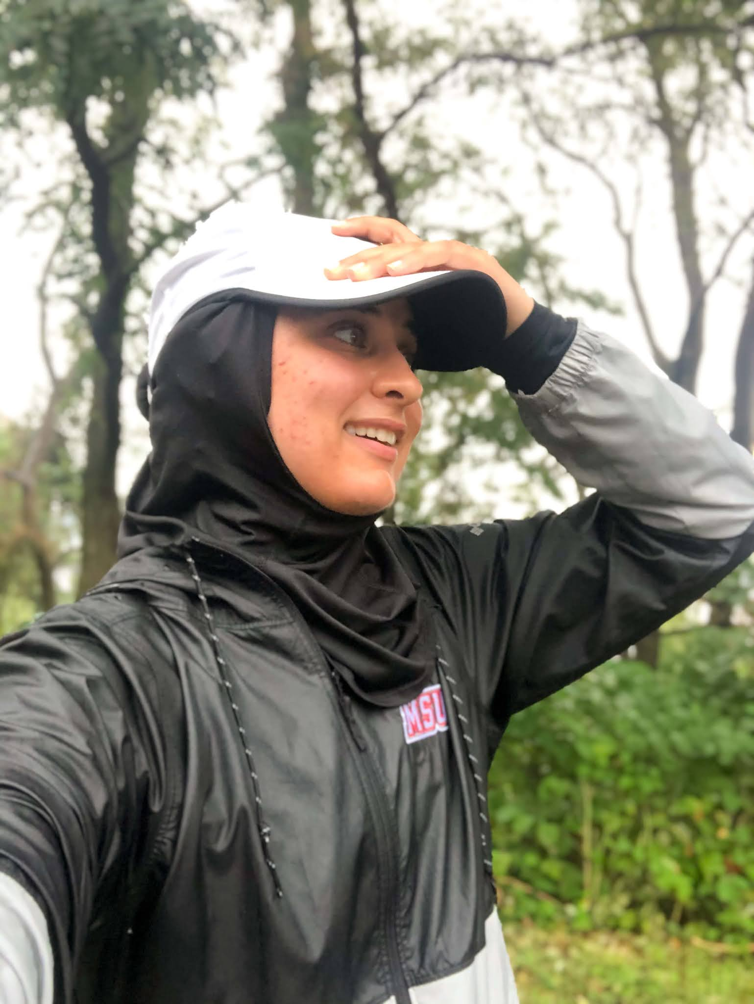 Sahara, in running rain coat with nike cap smiling head tilted away from camera; side profile