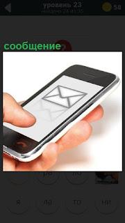 В руках у человека телефон, на котором пришло сообщение в виде конверта