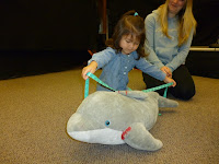Small girl uses measuring tape to measure length of a stuffed dolphin while her mother looks on.