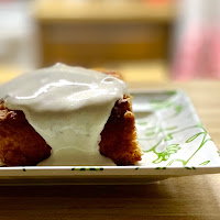 Slice of lemon cake with elderflower yogurt topping dripping on the side
