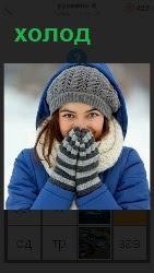 девушка в варежках греет руки теплом изо рта, так как холодно