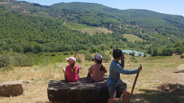 Three children sit on a big rock overlooking a Tuscan hillside