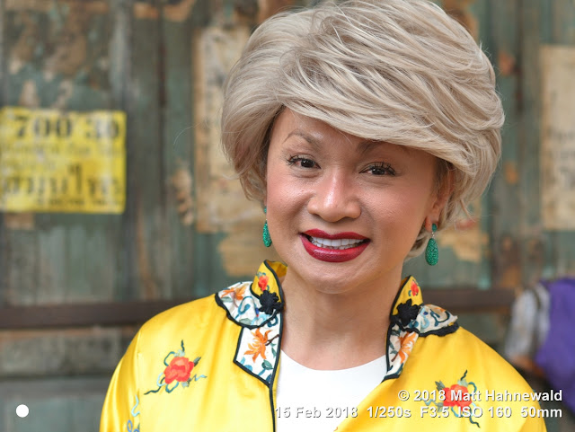 matt hahnewald photography; facing the world; cheongsam; yellow; character; head; face; makeup; eyes; laughing eyes; mouth; teeth; lips; lipstick; facial expression; eye contact; earrings; hair; hairstyle; consent; fun; travel; culture; lifestyle; beauty; fashion; chinese new year; urban; cultural; chinatown; bangkok; thailand; thai chinese; one person; female; male; man; woman; sexual ambiguity; transgender; genderqeer; ladyboy; shemale; ambiguity; uncertainty; tolerance; cross-dresser; lgbt; image; photo; backdrop; nikon d3100; nikkor af-s 50mm f/1.8g; prime lens; 50mm; 4x3; horizontal; street; portrait; closeup; head shot; seven-eighths view; outdoor; color; posing; authentic; smiling; beautiful; handsome; elegant; classy; gorgeous; charming