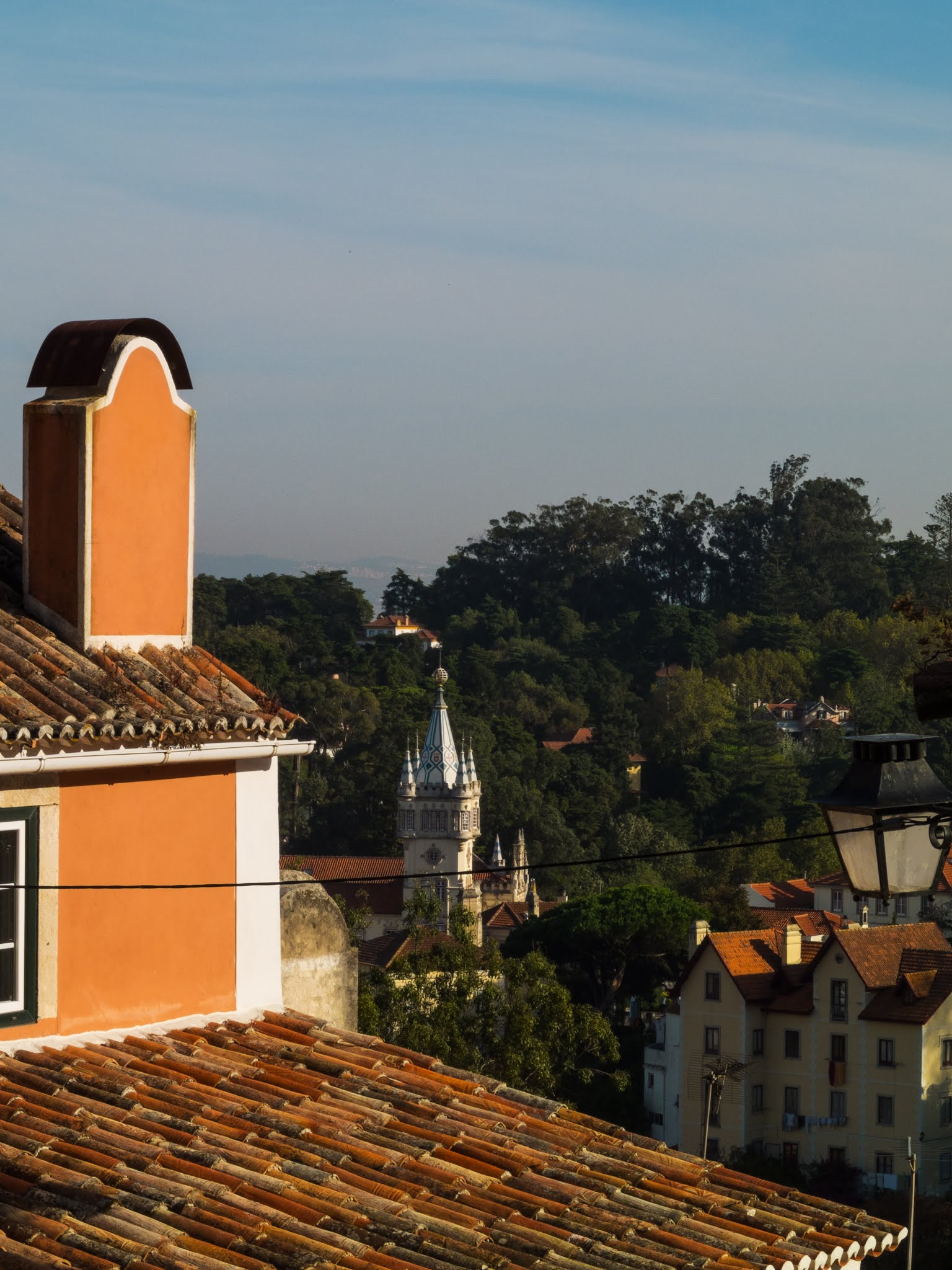 View of Sintra over a close up of a terracotta roof.