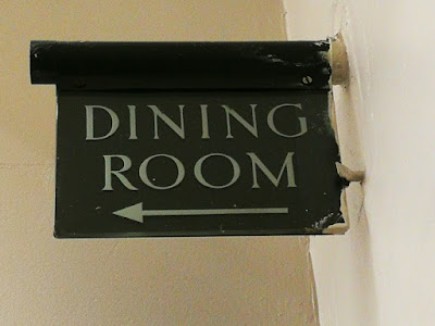 At the corner of two cream-painted walls, a round metal tube protrudes with a sign hanging from it. Both are dark brown, although marked on the right edge by cream paint left when the walls were repainted, and the sign says 'DINING ROOM' in pale letters with an arrow pointing left.