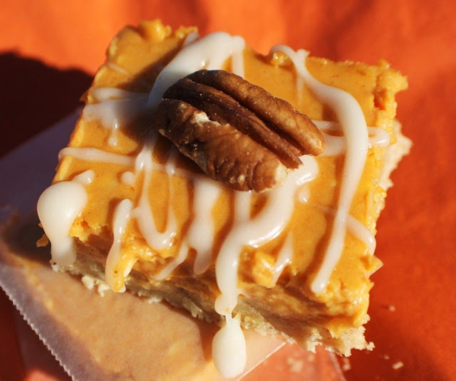 these orange colored bars are creamy pumpkin and the crust is made with a cake mix, there is a pecan on top and white swirl frosting