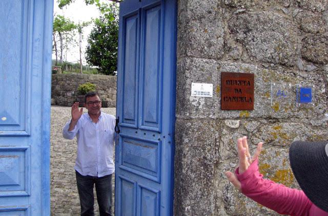 homem numa porta azul a sinalizar para uma mulher