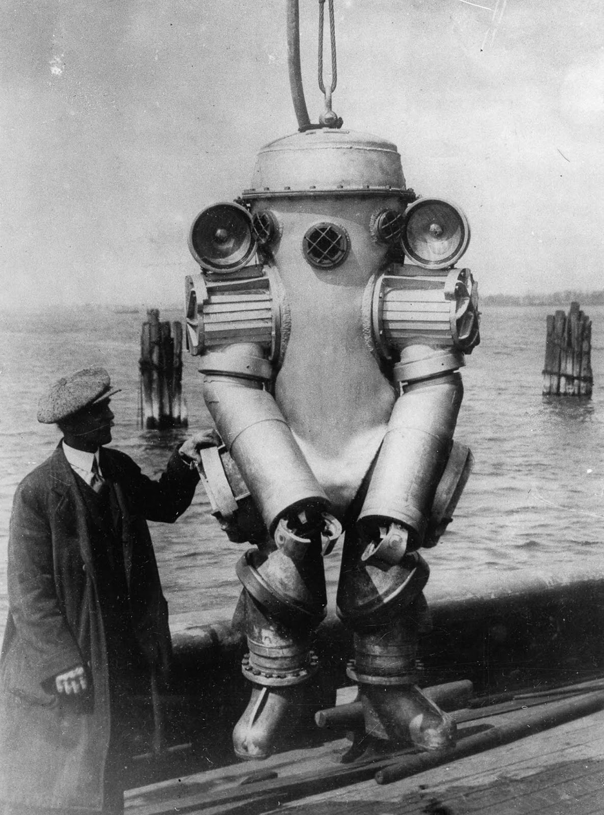 American inventor H.L. Bowdoin with his deep-sea diving suit, featuring shoulder-mounted 1,000-watt lamps and an integrated telephone. 1931.