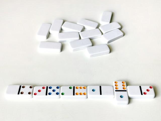 na zdjęciu dobino w kolorze kości słoniowej z kolorowymi kropkami, ustawione w rzędzie jak podczas gry, w tle widać kamienie do dobierania
