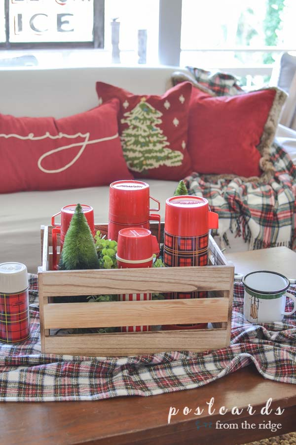 plaid blanket with wooden crate full of vintage red plaid thermoses and bottle brush trees