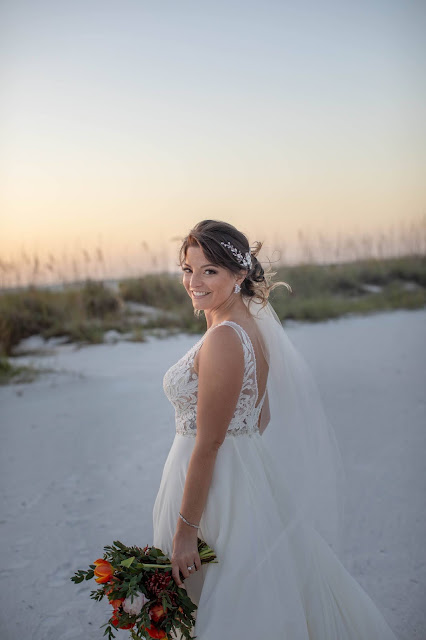 Bride smiling with floral bouquet after destination ceremony.
