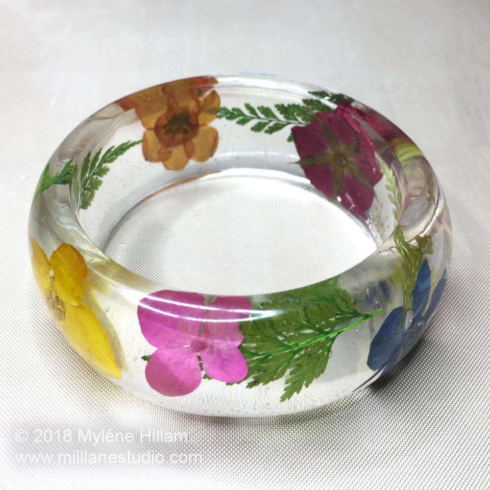 Dried spring flowers preserved forever in an epoxy resin bangle.