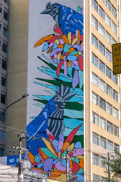 Mural na lateral de um edifício com gralhas-azuis