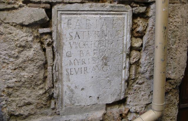 Pedestal del fòrum embegut en la façana d'una casa
