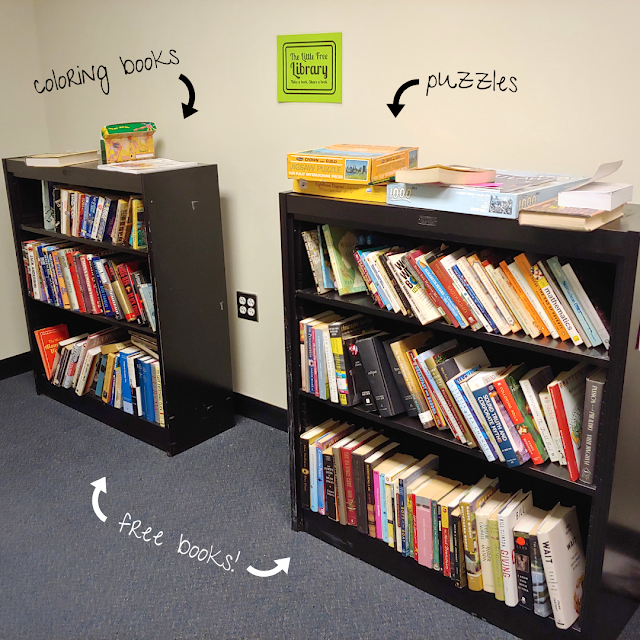 A photo of two small bookshelves. On top of one is a stack of coloring books; on top of the other is a stack of puzzles; and an added caption indicates that the books on the shelves are free to take.