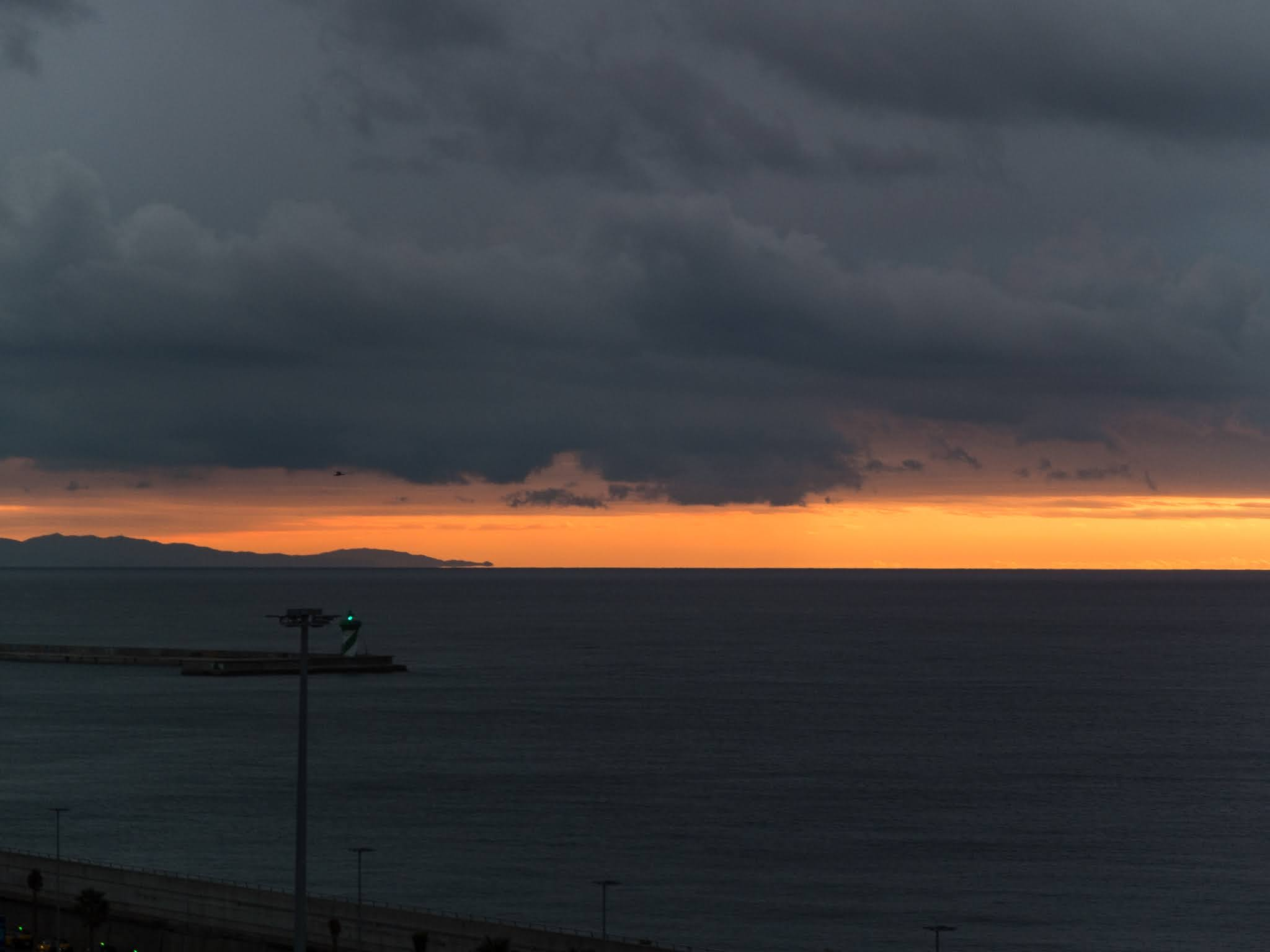 Dark clouds at sunrise in the port of Barcelona looking out towards the sea.