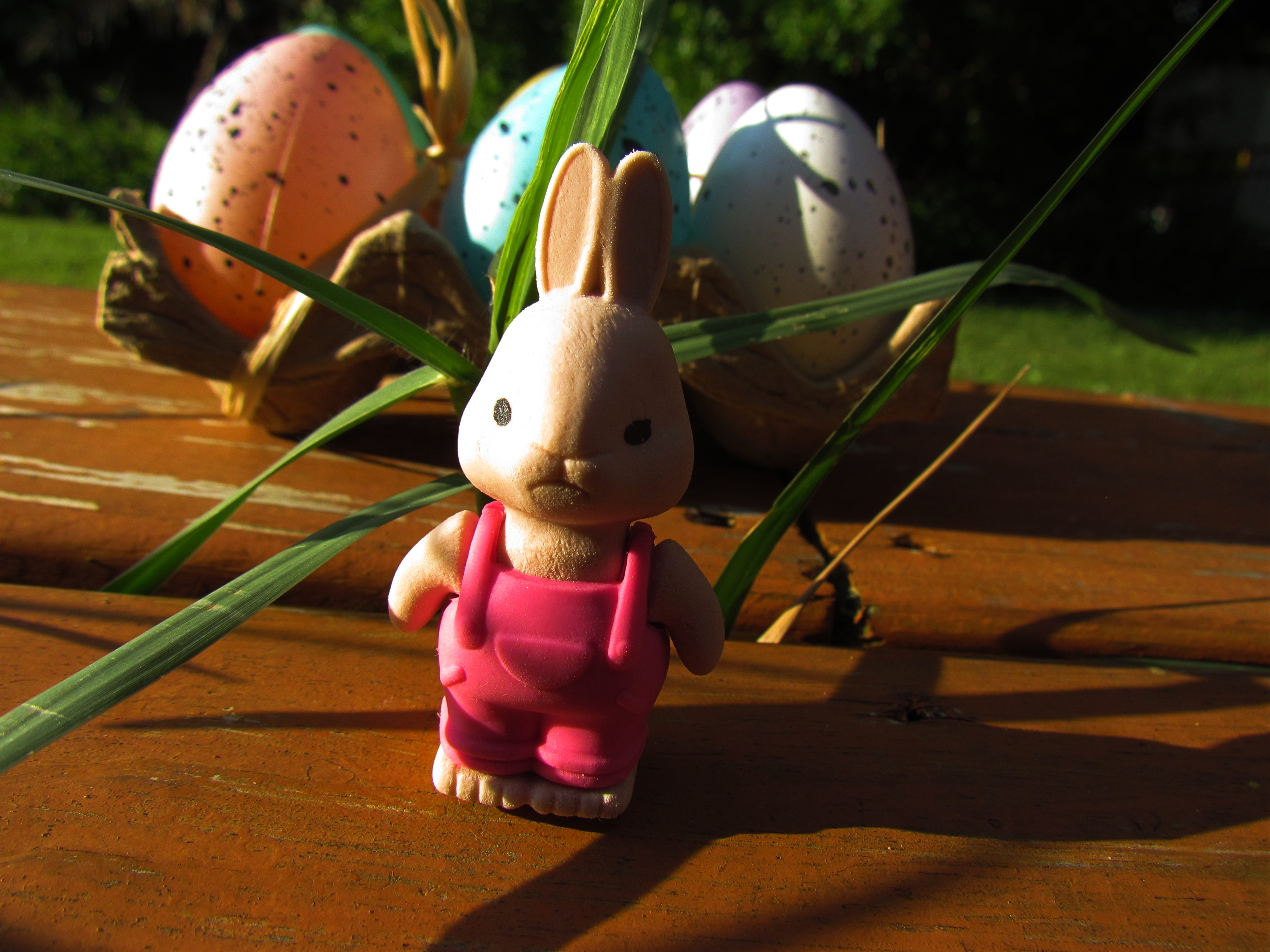 An Easter bunny figurine with pink overalls and speckled Easter Eggs and Egg Crate, Ostara Holidays