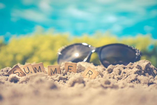 """Sunglasses and Scrabble tiles spelling out """"SUMMER"""" on sand during a sunny day."""