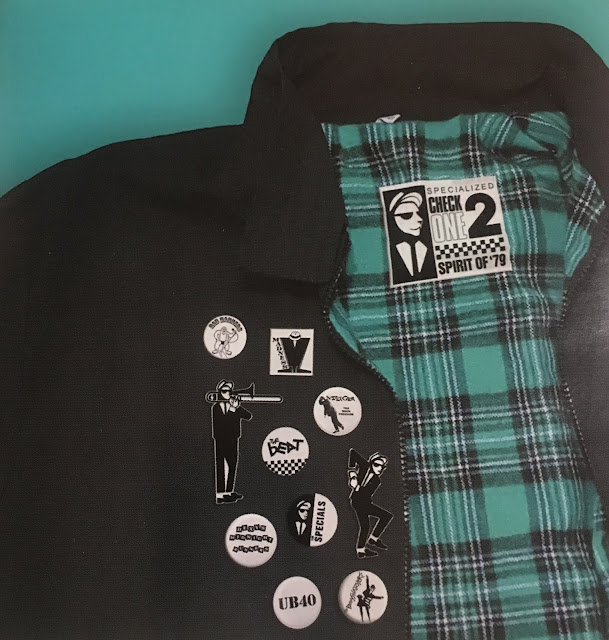 A harrington jacket is covered with badges for The Specials, The Beat, The Selecter, and other 2 Tone bands.