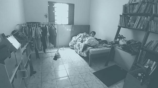 Foto com filtro cinza azulado, mostrando um quarto bagunça e meu filho me olhando da cama.