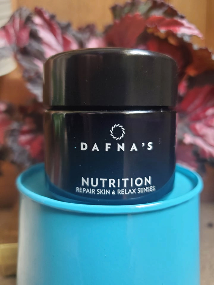 Dafna's Skincare Nutrition Moisturiser on a light blue stand with leafy red and black begonia behind