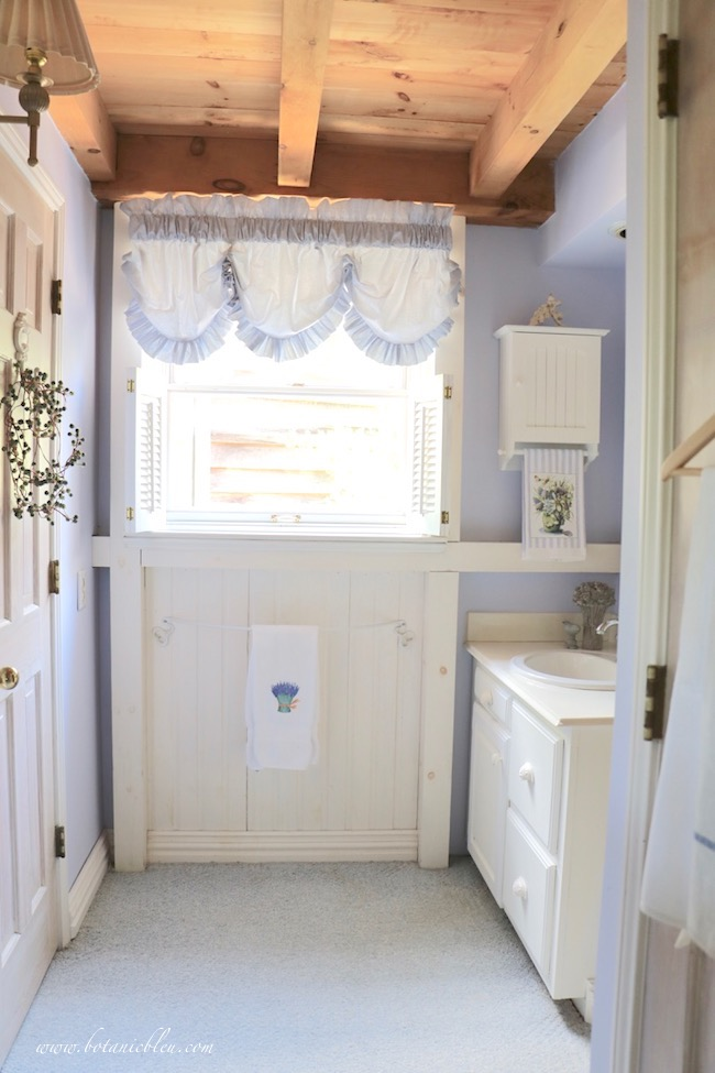 small white vanity area in master bathroom with natural wood and joist ceiling  AFTER vanity and baseboards painted