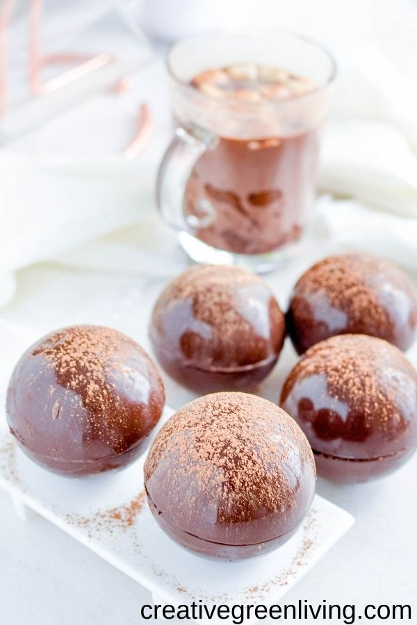 DIY homemade hot cocoa bombs filled with marshmallows and topped with cocoa powder near a mug of hot chocolate