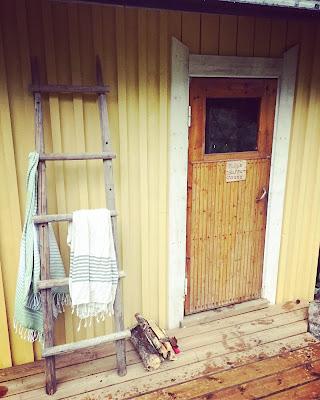 keltainen sauna, heinäseipäistä tehdyillä tikkailla pyyhkeitä ja vanha sormipaneelinen ovi