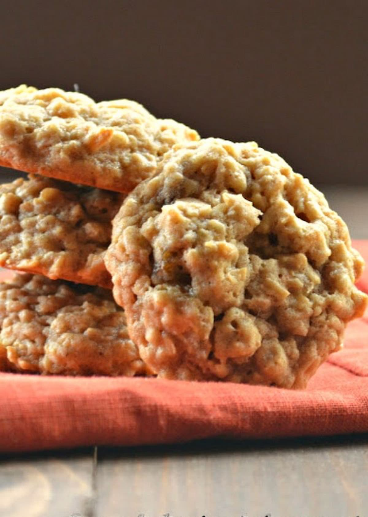Chewy Spicy Oatmeal Raisin Cookies on an orange napkin.