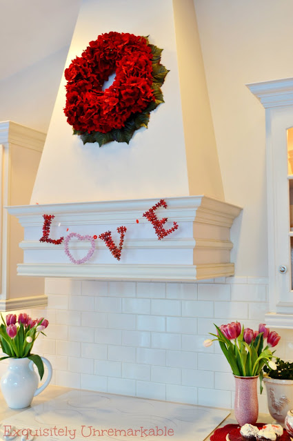 Love Banner For Valentines Day hanging on a kitchen hood with tulips on the counter in vases and a red hydrangea wreath hanging above