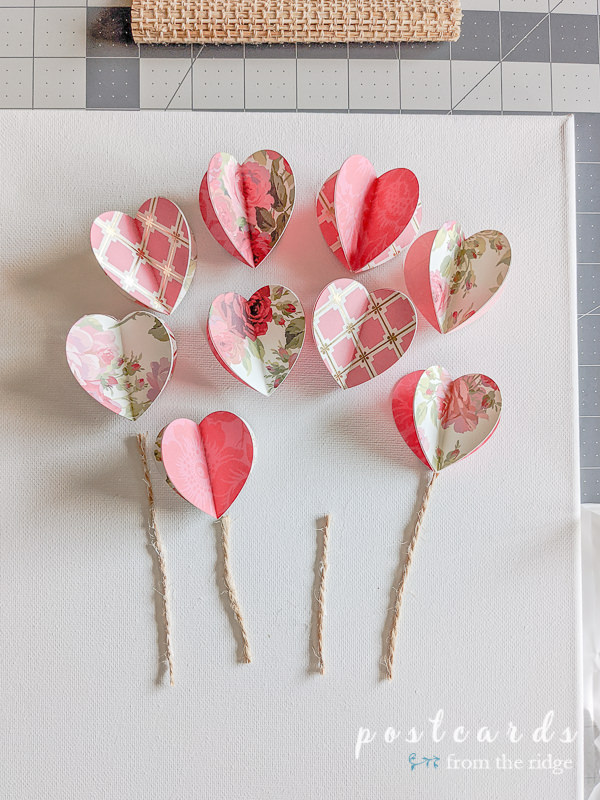 3-d floral paper hearts and pieces of twine on white canvas
