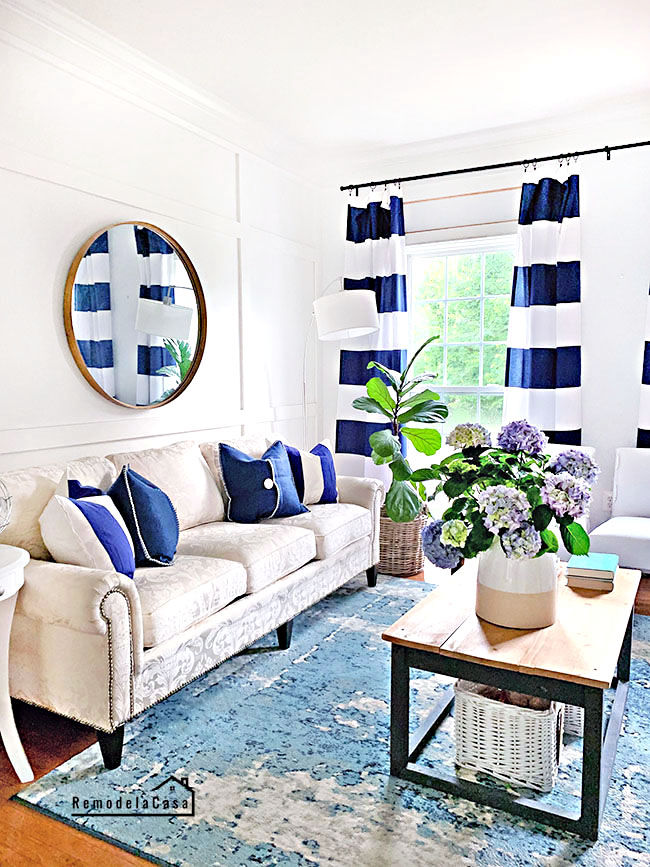 white and navy living room decor with hydrangeas and round gold mirror