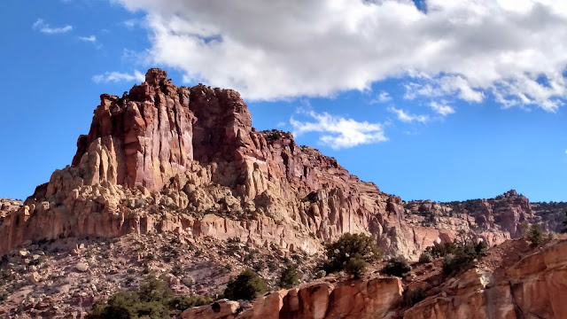 Big red mountain with blue sky and white clouds.