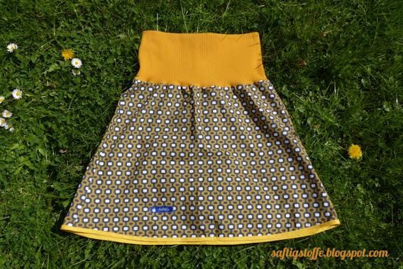 Knielanger Rock mit gelbem Bündchen am Bauch und gelbem Rocksaum. Stoff in 70er Retro-Muster