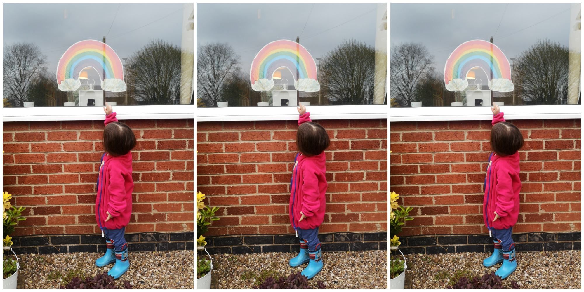 A picture of a toddler pointing at a rainbow they made during lockdown