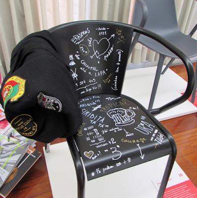 Uma cadeira portuguesa da Adico com inscrições de alunos universitários junto com uma capa do traje