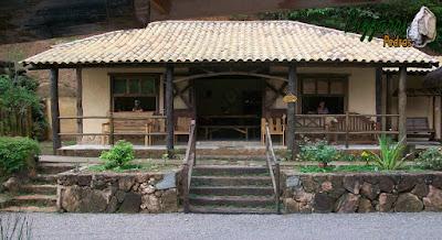Base com pedra na construção da cabana rústica com os pilares de madeira, a escada de dormente e o muro de pedra rústico.