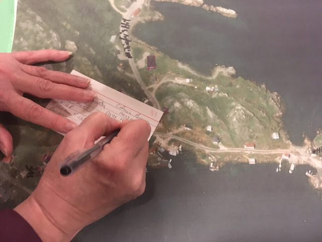 hands holding a pen, making notes on a map of the town of Salvage, Newfoundland