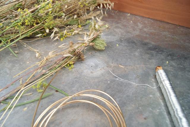 Wiesenblumen und Gräser werden um einen Draht gewickelt.