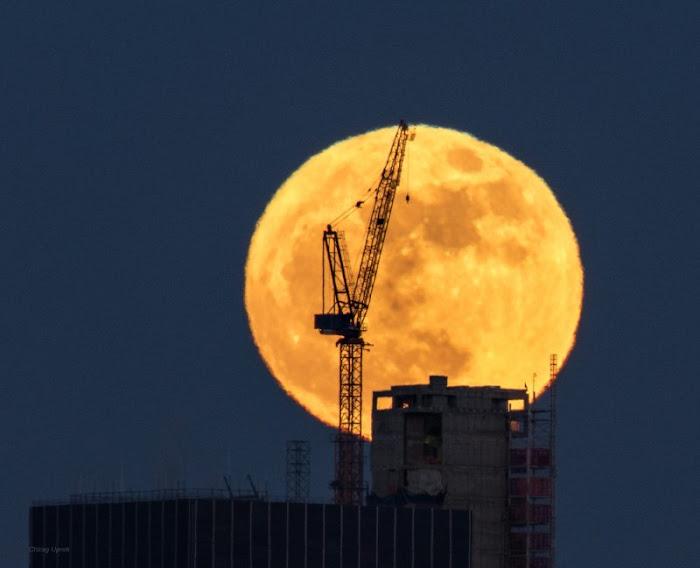 Mặt Trăng khuất phía sau một công trình đang được xây dựng ở Mã Nhật Tân, Nữu Ước. Nhiếp ảnh gia Chirag Upreti cho biết ông đứng từ xa và phóng to lên để chụp hình ảnh này, điều đó khiến tòa nhà vẫn có kích thước như bình thường nhưng Mặt Trăng có kích thước to hơn một cách ấn tượng.