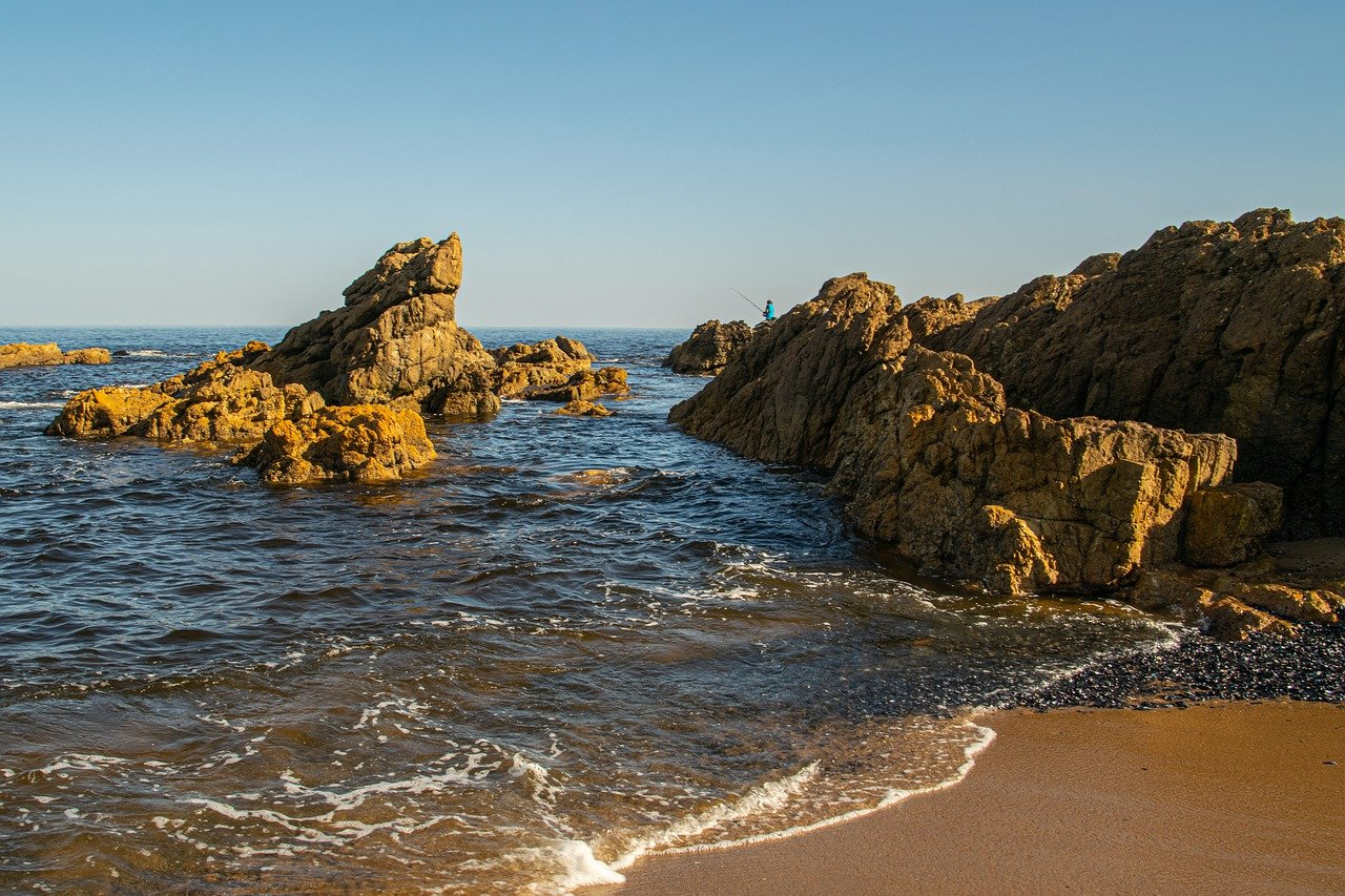 praia com varias pedras e aguas escuras