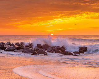 A wide perspective of waves crashing over rocks with the sun peeking over the horizon - Ocean Grove, New Jersey