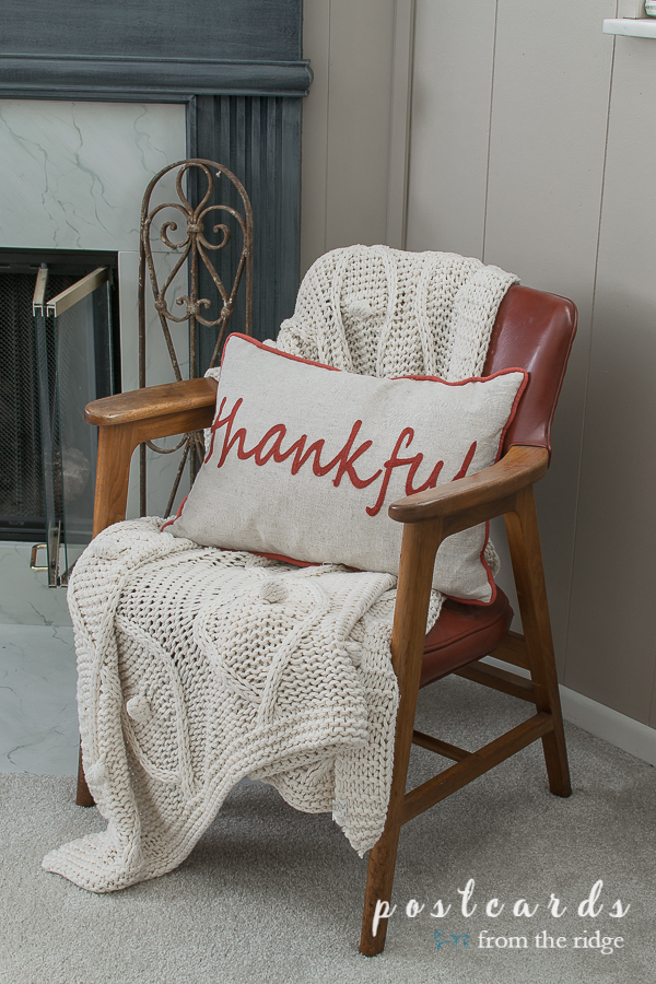 thankful pillow and cream throw blanket on mid century modern arm chair