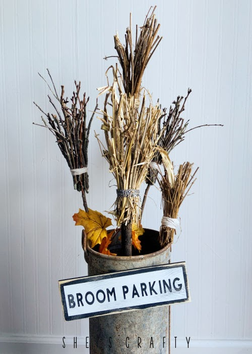 Twig brooms gathered in a planter with broom parking sign