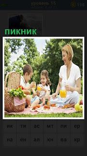 на природе на пикнике мама с детишками употребляют еду из корзины