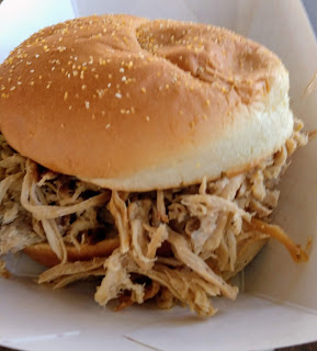 pulled pork peeks out of a bun, sitting in a white cardboat boat, from Black Dog BBQ in Mason City Iowa