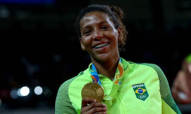 Rafaela Silva feliz posando para foto com a medalha de ouro na Rio 2016