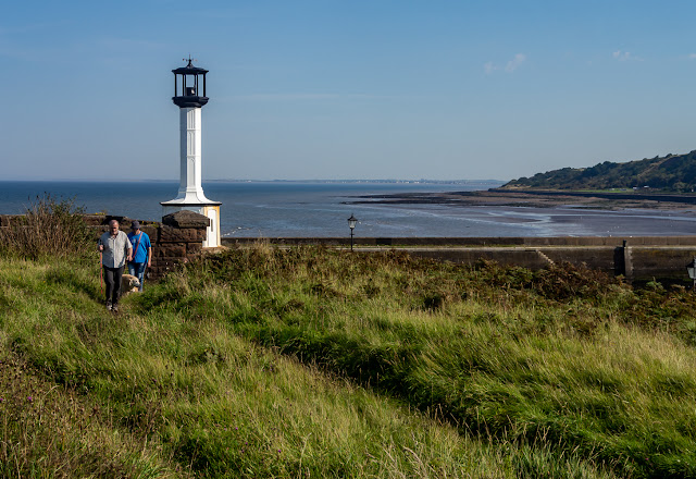 Photo of dog walkers on the old railway line by Maryport Lighthouse