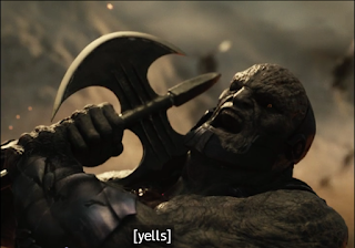 """Darkseid taking an axe to the shoulder. The closed caption says """"yells."""""""