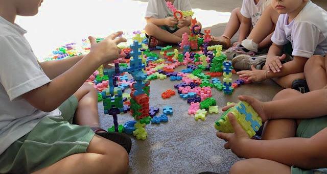 Meninos brincando de bloco de montar em rotina escolar na Educação Infantil